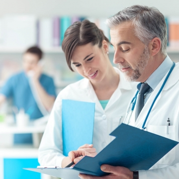 Confident doctor checking medical records on a clipboard with his female assistant, healthcare and professionalism concept